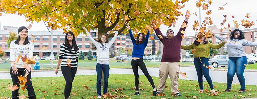 students on campus throwing leaves