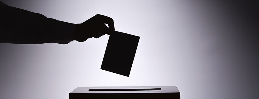 silhouette of hand dropping ballot in box