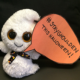 Stuffed ghost holding a sign that reads: stayghoulden this halloween