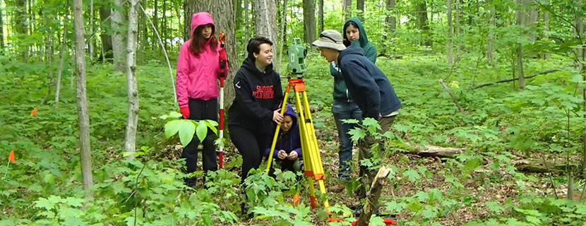 Student surveying in forest