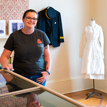 Spotlight story image pertaining to Female student in museum with army uniforms behind her