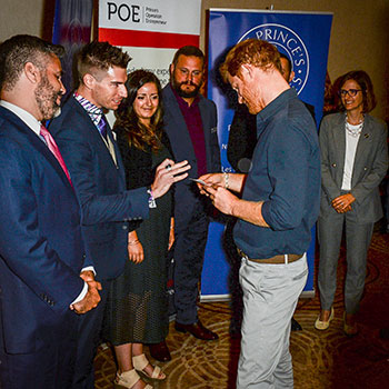 Spotlight story image pertaining to Alumnus Jeff Alpaugh hands Prince Harry a business card